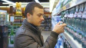 Väljande och köpande flaska för ung man av mineralvatten på supermarket Grabb som tar produkten från hyllor på livsmedelsbutiken arkivfilmer
