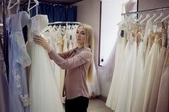 Väljer brud- mode för boutique, den härliga unga blonda kvinnan en klänning Royaltyfria Bilder