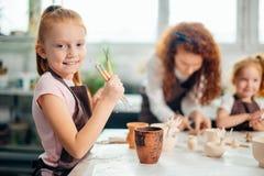 Väljer den near tabellen för flickaställningen och kniven för att arbeta med lera arkivbild