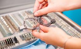 Väljer kvinnliga händer för optiker linser från uppsättningen av den korrigerande linsen som indikerar på plattorna av formen: ko arkivbild