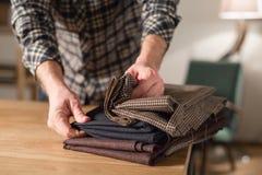 Väljer ull från bunten Arbete för ung man som en skräddare och använda en symaskin i seminarium arkivfoton