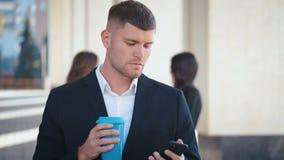 Välklädd företagare som står på sitt kontor Drick kaffe för att gå Skriva meddelande på sin smartphone Människor lager videofilmer