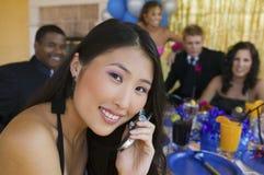 Välklädd tonåringflicka som använder mobiltelefonen på skoladansen arkivbilder