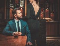 Välklädda par i lyxig lägenhetinre Royaltyfria Bilder