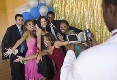 Välklädda tonåringar som poserar för videokamera på skoladansen royaltyfri bild