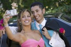 Välklädda tonårs- par som tar bilden utanför bilen royaltyfria bilder