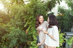 Välklätt le för lyckliga vänner för unga kvinnor, medan stå till Arkivbilder