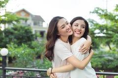 Välklätt le för lyckliga vänner för unga kvinnor, medan stå till Royaltyfri Fotografi