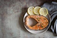 Välkokt laxbiff på en platta av citroner arkivbild
