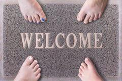 Välkommen dörr Mat With Funny Family Feet Vänliga Grey Door Mat Closeup med fyra kala fot stå Fyra fot på Arkivbild