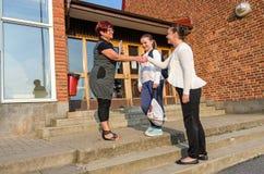 Välkommen handskakning mellan skolflickamodern och läraren Arkivbilder