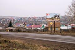 Välkommet bräde, innan att skriva in staden av Uzhur från söderna, mot bakgrunden av lantliga hus Arkivfoton