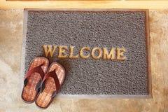Välkommet mattt med bruna sandaler Arkivfoto
