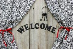Välkommet tecken med järntangenter och blom- gardiner Royaltyfri Foto