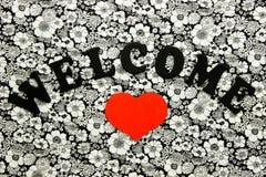 Välkommet tecken med stor röd hjärta på blom- bakgrund Arkivbilder