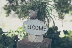 Välkommet tecken, på blommakrukan arkivbilder