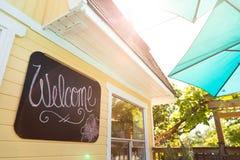 Välkommet tecken på en restauranguteplats med ett paraply och solen som skiner från över royaltyfria bilder
