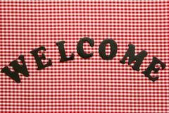 Välkommet tecken på röd rutig bordduk (för gingham) Royaltyfria Foton