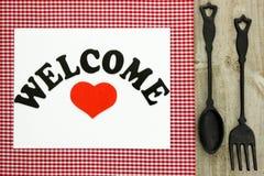 Välkommet tecken på röd rutig bordduk med den gjutjärnskeden och gaffeln Royaltyfri Fotografi