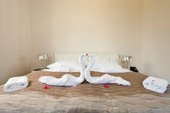 Välkomna svanen från vita handdukar på säng royaltyfri fotografi