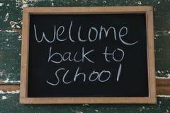 Välkomna tillbaka till skolatext som är skriftlig på den svart tavlan Royaltyfri Foto