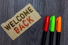 Välkomnande för ordhandstiltext tillbaka Affärsidéen för varma hälsningar ankom beträffande för nöjd Paperboard för repetition gä arkivbild