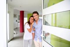 Välkomnande folk för lyckliga par hemma arkivbild