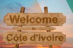 Välkomnande till den `-Ivoire för skjul D allsången på wood bakgrund med att blanda nationsflaggan Royaltyfria Bilder
