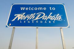 Välkomnande till det legendariska tecknet för North Dakota vägtillträde royaltyfri fotografi