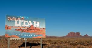 Välkomnande till det Utah tecknet med butten i bakgrunden arkivfoto