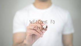 Välkomnande till Grekland, manhandstil på den genomskinliga skärmen Royaltyfri Fotografi