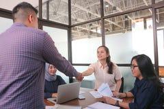 Välkomnande till laget! män som skakar händer till kvinnan och ser de med leende medan deras coworkers som sitter på affären royaltyfri foto