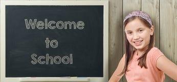 Välkomnande till skolan som är skriftlig på svart tavla med unga flickan royaltyfria bilder