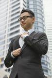 Välla fram den klädda asiatiska affärsmannen som justerar hans halsband Royaltyfria Bilder