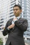 Välla fram den klädda asiatiska affärsmannen som justerar hans halsband Arkivbild