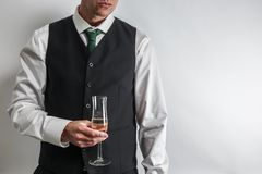 Välla fram den klädda mannen som rymmer ett exponeringsglas av champagne, rostat bröd/bifall royaltyfri fotografi