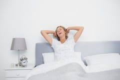 Välla fram den utvilade blonda kvinnan som sträcker och gäspar i säng Arkivbild