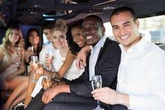 Välla fram klätt folk som dricker champagne i en limousine royaltyfria bilder