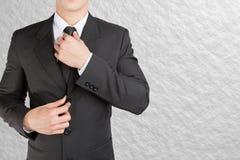 Välla fram looklike smart för klädd affärsman justera hans halsband royaltyfria bilder