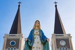Välsignad jungfruliga mary staty och kyrka royaltyfria foton