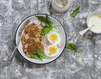 Välsmakande hela kornpannkakor, kokt ägg och nya spenat och rädisor på emaljplattan på stentexturen Royaltyfri Bild