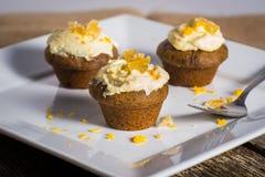 Välsmakande ljust rödbrun muffin med gräddostglasyr på kaka Arkivbild