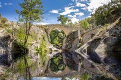Välva sig bro som göras av stenar - reflexionsplats royaltyfria foton