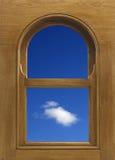Välva sig den formade wood fönsterramen med det vita molnet i blå himmel Arkivfoton