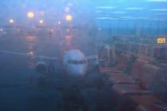 Välvat flygplan på den Don Mueang flygplatsen till och med portfönstret Reflektera av spegeln i port Fotografering för Bildbyråer