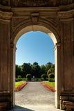 Välvd dörröppning som leder till en formell trädgård Arkivfoto