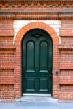 Välvd dörr för arv i röd tegelstenvägg Royaltyfria Bilder
