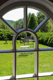 Välvd fönstersikt av den trädgårds- uteplatsen arkivbilder