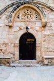 Välvd ingång till den gamla kyrkan Inom tända stearinljus och lampor Royaltyfri Fotografi