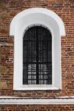 Välvt fönster med stänger, som delen av en forntida byggnad Arkivbild